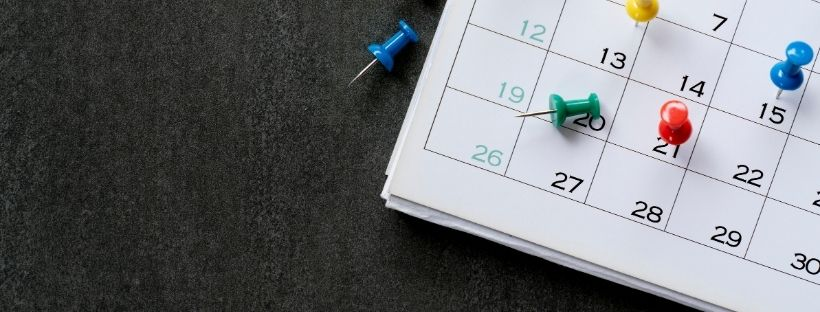 A picture of a monthly calendar on the table with pins